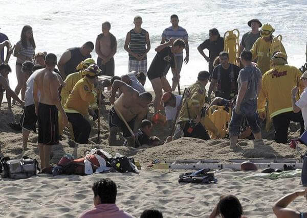 July 21: photo released by the Half Moon Bay Review shows emergency crew workers and volunteers working to rescue a man at Francis State Beach in Half Moon Bay, Calif. Authorities say a young man has died after a hole he dug on a Northern California beach collapsed and trapped him in the sand for at least five minutes.AP Photo/Half Moon Bay Review, Dean Coppola