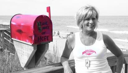 Sue Goodrich poses with the first Little Red Mailbox in Kill Devil Hills. Photo OBX Beach Bum.